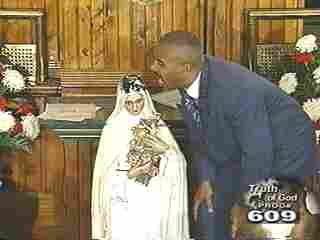 Pastor Gino Jennings and statue of Mary, sorry Saint Therese of the Child Jesus